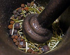 Bruk rikelig med krydder: Rosemarin, hel pepper, einerbær og flaksalt som støtes i en morter.